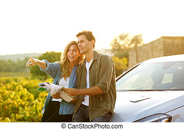 couple sitting on car with map and woman pointing