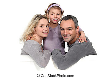 portrait of couple with daughter against studio background