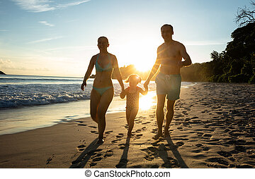 Portrait Of Couple With Her Daughter Walking On The Beach