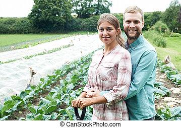 Portrait Of Couple Working In Organic Farm Field