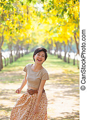 beautiful asian woman standing in blooming flowers park with happiness emotion