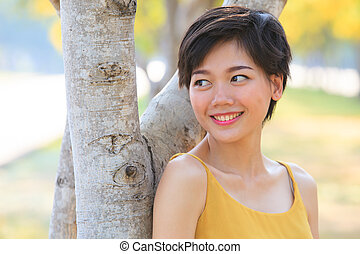 portrait of couples beautiful asian woman standing in blooming flowers park with happiness emotion