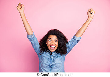 Portrait of crazy funky afro american girl hear unbelievable lottery win news impressed scream wow omg raise fists wear casual style clothing isolated over pink color background