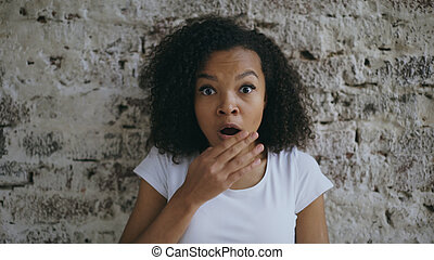 Portrait of curly african american teenager girl actively surprising and wondering on brick wall background