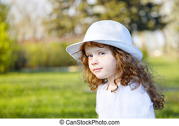 Portrait of curly girl in a white hat.