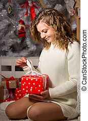 Portrait of curly woman unpacking red Christmas gift box