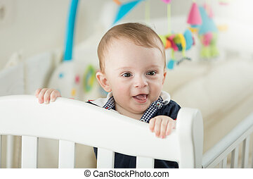 Portrait of cute 1 year old baby boy standing in cot