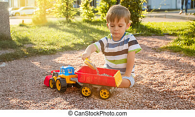 Portrait of cute 3 years old toddler boy sitting on the playground at park and playing with colorful plastic toy truck. Child having fun and playing outdoors with toys