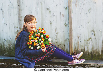 Portrait of cute 8-9 year old girl, holding bright bouquet of colorful fresh tulips, sitting against white wooden background