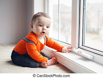 Portrait of cute adorable Caucasian baby boy sitting on windowsill looking away