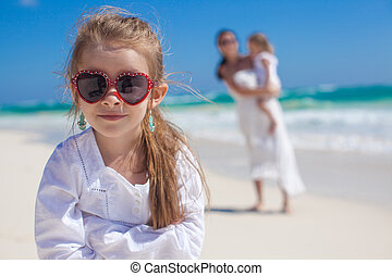 Portrait of cute adorable girl and her mother with little sister in the background at tropical beach
