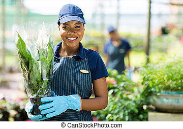 african american female gardener holding a plant