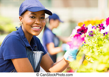 african female florist working in nursery