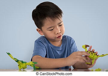 Portrait of cute asian boy playing with colorful plastic toy bricks at the table
