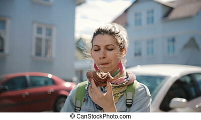 Portrait of cute attractive woman standing on street and eating the baked bun. Hungry female take a break on fast food.