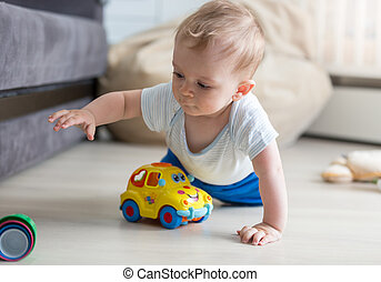 Portrait of cute baby boy crawling on floor and playing with...