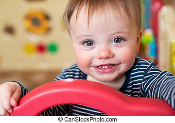 Portrait Of Cute Baby Boy Looking Out Of Play Pen And Smiling At Camera