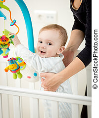 Portrait of cute baby boy playing with carousel in crib