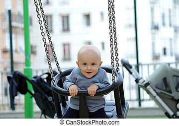 Cute Baby Boy Sitting On A Swing In Park