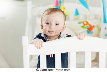 Portrait of cute baby boy standing in white wooden crib and looking in camera