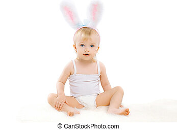 Portrait of cute baby in costume easter bunny with fluffy ears on a white background