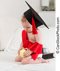 Portrait of cute baby in graduation cap holding apple. Concept of baby education