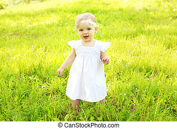 Portrait of cute baby walking on the grass in sunny summer day