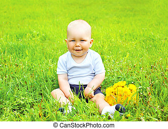 Portrait of cute baby with yellow dandelion flowers sitting on the grass in sunny summer day