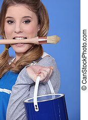 portrait of cute blonde painter holding brush between teeth against blue background