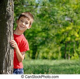Portrait of cute boy standing near the tree in park