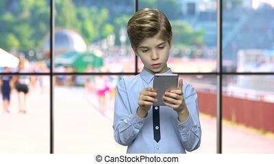 Portrait of cute boy using smartphone.