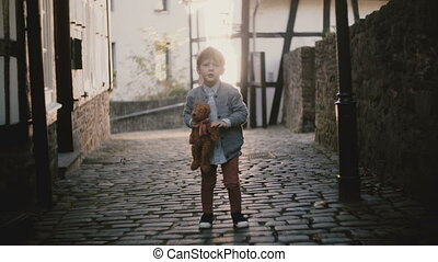 Portrait of cute Caucasian boy singing outside. Male child...