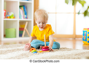 Portrait of cute child toddler boy assembling colorful pyramid toy on floor at living room