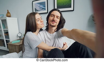 Portrait of cute couple making online video call in bed at...