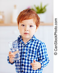 portrait of cute cute toddler baby boy drinking fresh water from glass early in the morning in pajamas