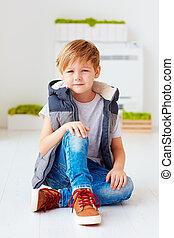 portrait of cute fashionable kid, boy sitting on the floor