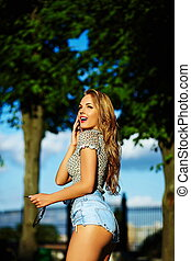 portrait of cute funny sexy young stylish smiling surprised woman girl model in bright modern cloth with perfect sunbathed body outdoors in the park in jeans shorts