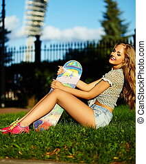 portrait of cute funny sexy young stylish smiling woman girl model in bright modern cloth with perfect sunbathed body outdoors in the park in jeans shorts with skateboard