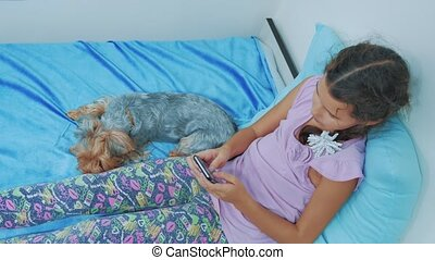 Portrait of cute girl and dog pet lying on the bed with...