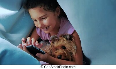 Portrait of cute girl and dog pet under blanket with...