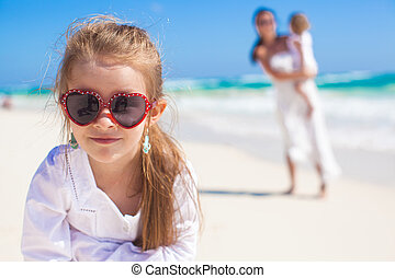 Portrait of cute girl and her mother with little sister in the background at tropical beach