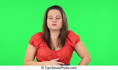 Portrait of cute girl goting a cold and sneezing. Chubby girl in a coral dress with straight hair medium length and light eyes on green screen at studio