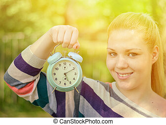 Portrait of cute girl holding old clock
