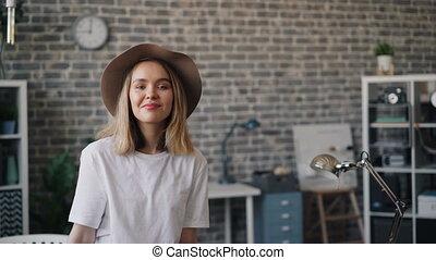 Portrait of cute girl in hat standing in office alone...