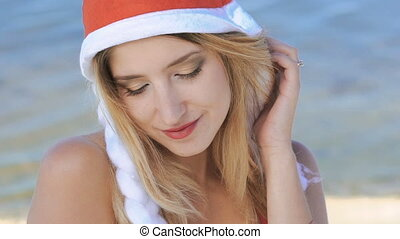 Portrait of cute girl in santa hat smiling. Slowly