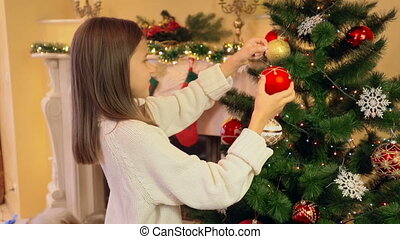 Portrait of cute girl in sweater decorating Christmas tree with baubles
