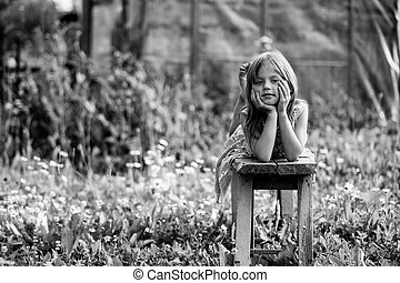 Portrait of cute girl in the yard of a country house. Black and white photo.