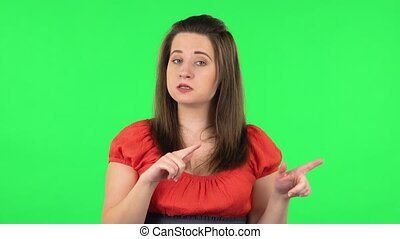Portrait of cute girl is reporting a lot of interesting information. Chubby girl in a coral dress with straight hair medium length and light eyes on green screen at studio