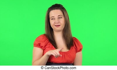 Portrait of cute girl smiling and showing heart with fingers then blowing kiss. Chubby girl in a coral dress with straight hair medium length and light eyes on green screen at studio