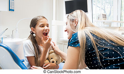Portrait of cute girl showing teeth to her mother in dentist office